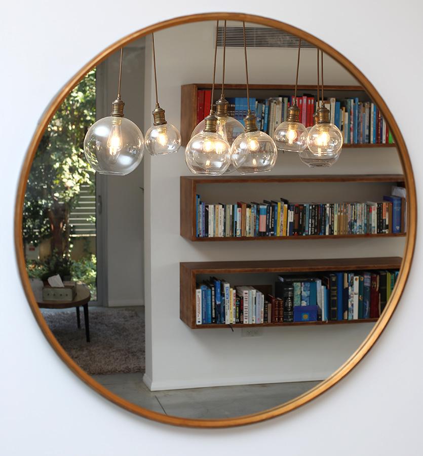 מראה עגולה מפליז ומנורות תלייה לסלון