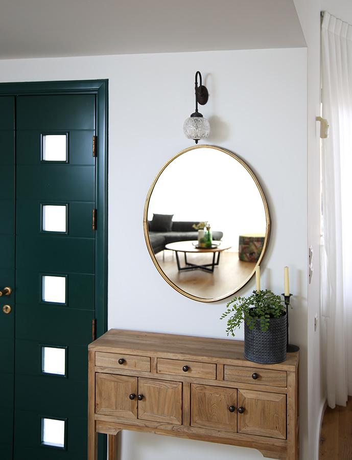 קונסולת כניסה עם מראה עגולה וגוף תאורה צמוד קיר